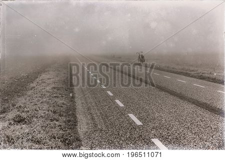 Old Black And White Photo Of Bicycle Standing Aside Rural Road In Mist.