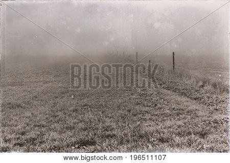 Old Black And White Photo Of Farmland With Fence In Mist.