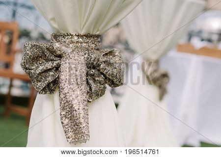 Bow-knot with sequins as a wedding ceremony decoration for the table cloth