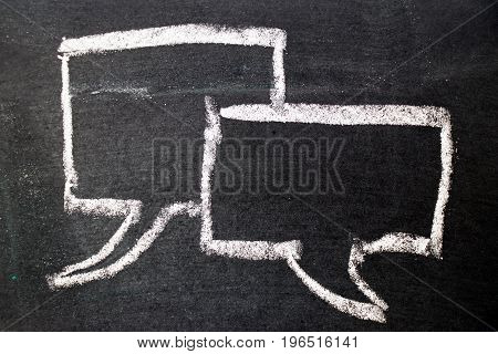 White chalk drawing as bubble speech on black board background (Concept as online chat thinking talking with customer)