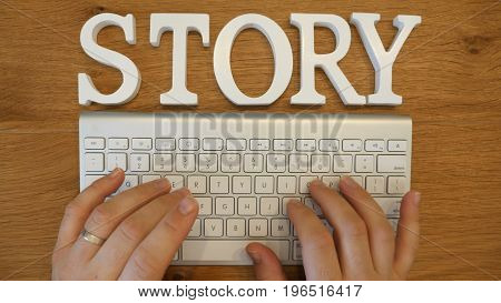 Story concept with hands typing on a white computer keyboard conceptual of journalism and reporting or of an author and writer