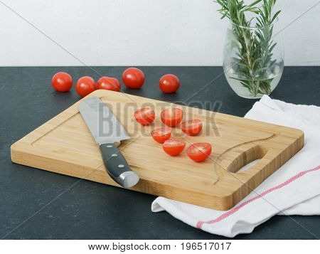 Sliced cherry tomatoes on a cutting board. Cooking food.