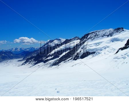 SWISS ALPS, snow covered high alpine mountains range landscape seen from Jungfrau in SWITZERLAND with clear blue sky in warm sunny summer day: CANTON OF BERN EUROPE on JULY