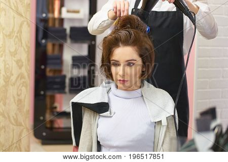 Caucasian woman at the hairdresser. Hairdressing salon customer. Hair styling tips.