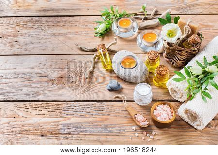 Spa still life wellness setting concept. Assortment of essential oil cream sea salt natural soap candles and towel on a rustic wooden table. Copy space background