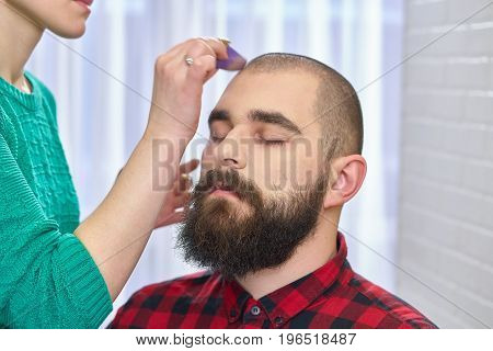 Bearded man getting makeup. Hand of visagist using sponge.