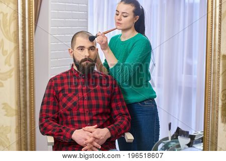 Bearded model and makeup artist. Visagist at work.