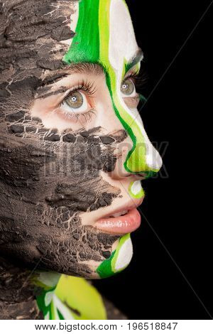 Close up portrait of woman with extreme make up on black background in studio photo. On stage beauty image. Conceptual make-up
