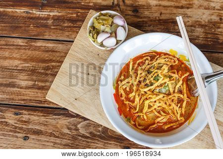 Curried noodle soup (Khao soi) with chicken meat and spicy coconut milk on wood table. Thai food cuisine northern style in Chiang Mai Thailand.