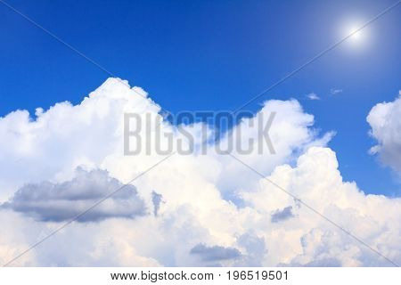 Blue sky background with white clouds and sunshine on sunny summer or spring day.
