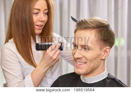 Man at the barber smiling. Happy guy in hair salon. Stylish haircuts for men.