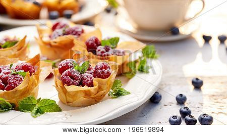 Phyllo cups with Mascarpone filling topped with raspberries on a white plate
