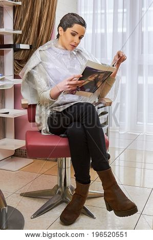 Woman in hair salon reading. Young female holding a magazine. Latest fashion articles.
