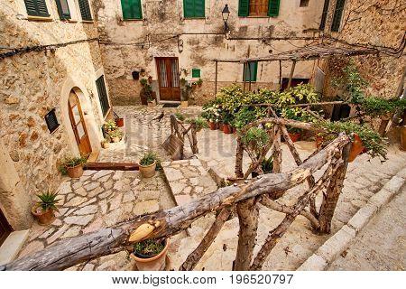 Old European street decorated with fresh flowers city of Valldemossa. Palma de Mallorca. Spain