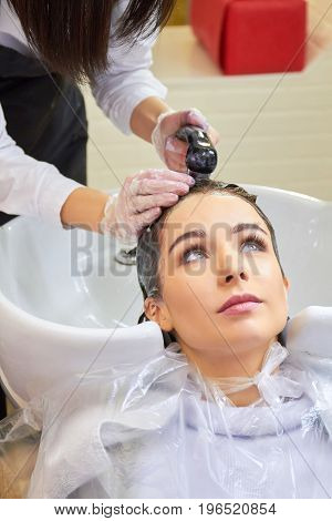 Young woman getting head washed. Beautician rinsing hair after dying.