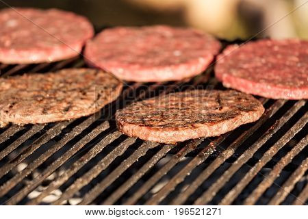 Some raw and cooked hamburgers on grill