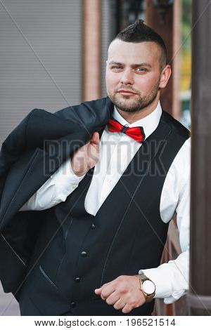Young stylish man in a suit. Portrait of the groom. The groom is holding his jacket on his shoulder look at the camera. Hand with golden watch. Business concept.