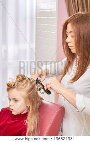 Hairdresser and child. Hairstylist at work, curling iron.