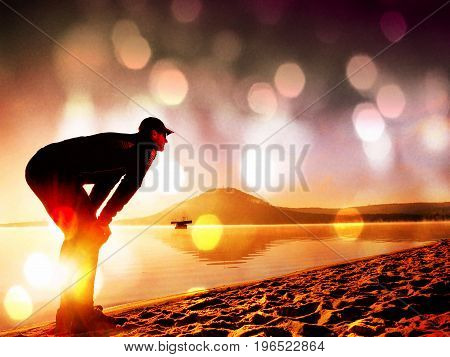 Film Effect. Man Exercising On The Beach.  Silhouette Of Active Man Exercising  And Stretching On Th