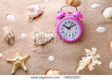 Pink Alarm Clock With Seashells On Beach Sand