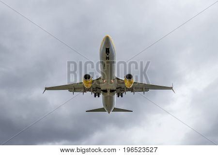 Overhead view of passenger airplane short before landing. Overcast cloudy sky.
