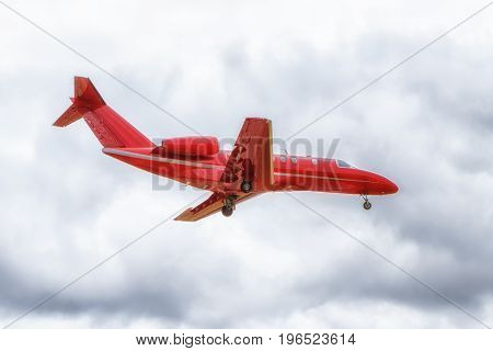 Overhead view of a red business jet airplane short before landing. Overcast cloudy sky.