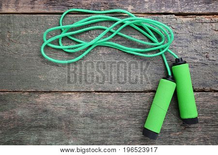 Green skipping rope on the wooden table
