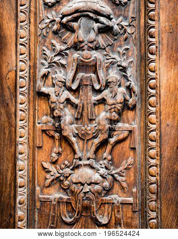 Detail of old wooden gate engraved with demonic figures.