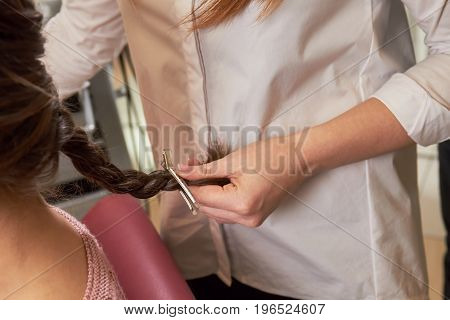 Hairdresser holding braid. Female hair with barrette.