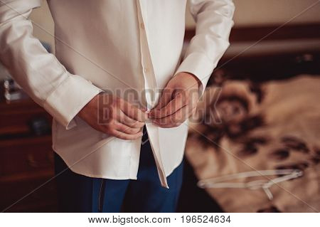 Man Buttoning His Shirt