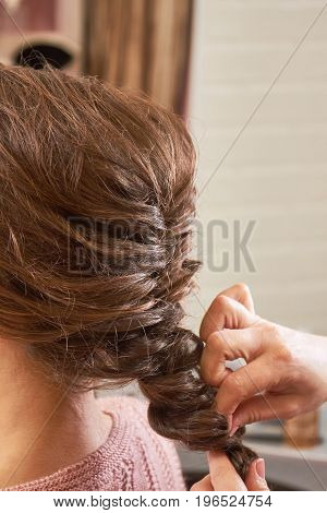 Hands of hairstyist plaiting braid. Female hairdo macro.