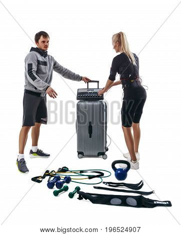 Blonde fitness woman in full electrical muscular stimulation suit and her trainer setting parameters of EMS station. Various sport gear like kettlebells dumbbells belts and expanders around them. Studio photo isolated on white background.