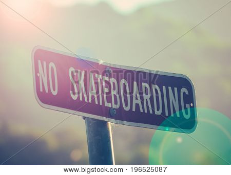 Retro Style Photo Of A No Skateboarding Sign At Sunset With Lens Flare