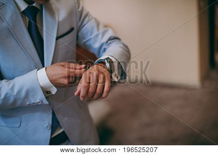 A Man Putting On Watch. The Bridegroom At The Wedding With The Clock