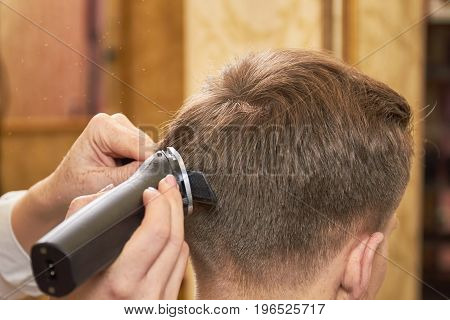 Man getting haircut close up. Hands, comb and hair clipper.