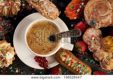 Delicious pastries with a cup of hot coffee. A colorful berry eclairs with strawberries blackberries currants on black table. Top view close up