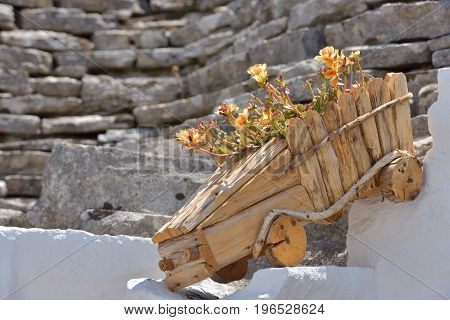 Wood flowerpot with colorful flowerson old exterior stone house in close up view