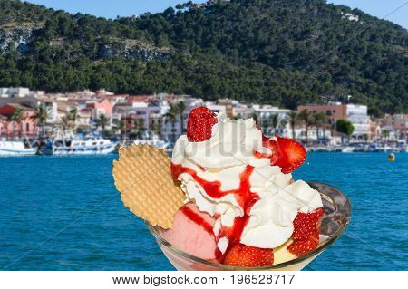 Strawberry sundae with fresh strawberries and cream in the background a beautiful Mediterranean sea bay.