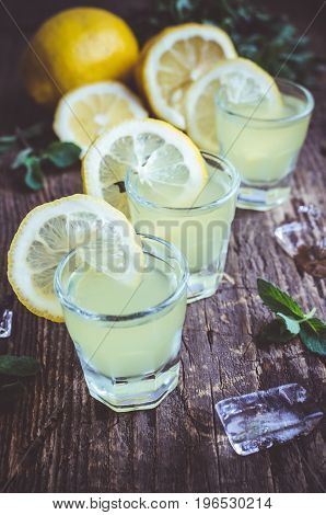 Traditional homemade lemon liqueur limoncello and fresh citrus on the old wooden background. Italian traditional liqueur limoncello with lemon. Italian alcoholic beverage. Selective focus and toned image.