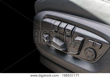 Power seat contol buttons of a passenger car modern car interior details