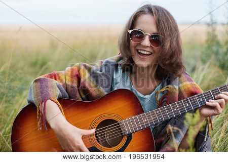 Happy Female Learning Playing Guitar While Sitting At Greenland Having Fun. Beautiful Woman Wearing
