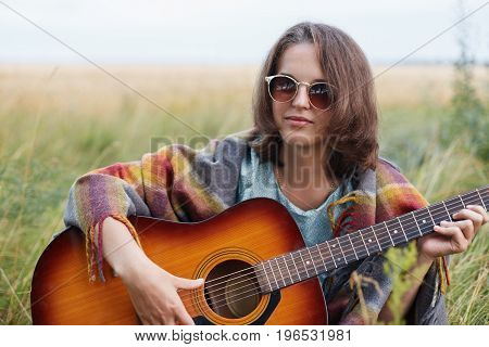 Serious Female With Attractive Appearance Wearing Sunglasses Sitting At Meadow With Acoustic Guitar