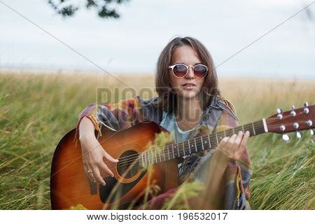 Romantic Woman With Short Straight Dark Hair Wearing Cape And Sunglasses While Resting At Green Fiel