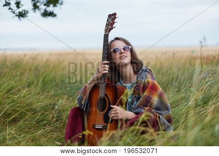 Horizontal Portrait Of Dreamy Female In Sunglasses Holding Acoustic Guitar Looking Upwards Dreaming