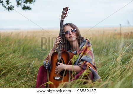 Portrait Of Talented Female Musician Sitting At Green Grass With Guitar Having Thoughtful Expression