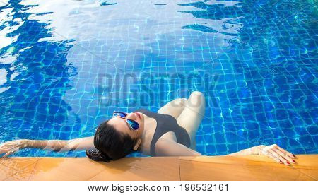 Women lifestyle relaxing near luxury swimming pool sunbath summer day at the beach resort in the hotel. Summer Concept