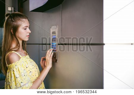Woman Dials An Apartment Code On An Electronic Doorphone Panel