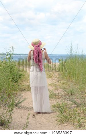 back of woman wearing hat on beach path