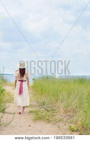 woman wearing hat walking on beach path