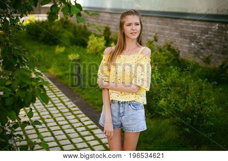 Young Beautiful Woman Is Strolling Outdoors In The Yard, Against The Backdrop Of Greenery And Houses